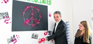 """Wilfried Oellers ließ es sich am """"Red Hand Day"""" nicht nehmen, auch seine Hand aus roter Farbe auf dem Plakat der Wohngruppe """"Momo"""" in Oberbruch zu hinterlassen, bevor er es mitnahm nach Berlin. Foto: Anna Petra Thomas"""